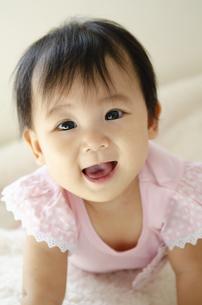 ベッドの上で笑っている赤ちゃんの写真素材 [FYI04118297]