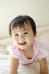 ベッドの上で笑っている赤ちゃんの写真素材 [FYI04118298]