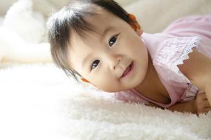 ベッドの上で笑っている赤ちゃんの写真素材 [FYI04118301]