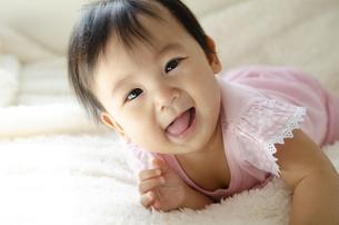 ベッドの上で笑っている赤ちゃんの写真素材 [FYI04118302]