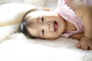 ベッドに寝転がって笑っている赤ちゃんの写真素材 [FYI04118308]