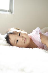 ベッドに寝転がっている赤ちゃんの写真素材 [FYI04118312]
