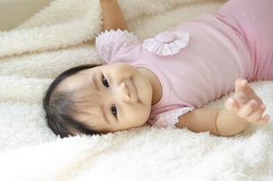ベッドに寝転がっている赤ちゃんの写真素材 [FYI04118314]