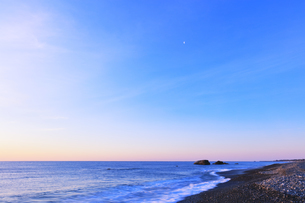 浜辺に寄せる波と朝焼け空に月の写真素材 [FYI04118378]