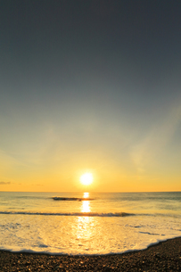 浜辺に寄せる波と朝日の写真素材 [FYI04118381]