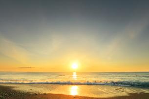 浜辺に寄せる波と朝日の写真素材 [FYI04118382]