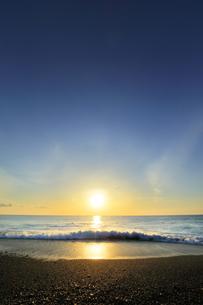 浜辺に寄せる波と朝日の写真素材 [FYI04118383]