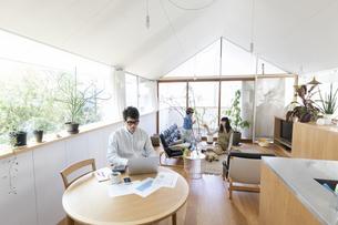 自宅で仕事をする男性とその家族の写真素材 [FYI04118518]