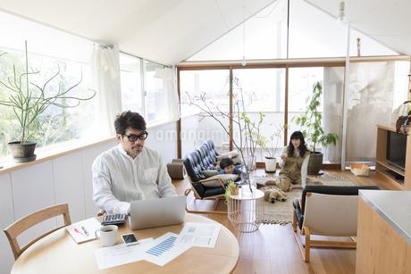 自宅で仕事をする男性とその家族の写真素材 [FYI04118521]