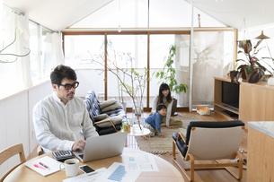 自宅で仕事をする男性とその家族の写真素材 [FYI04118524]