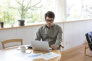 自宅でパソコンを使う男性の写真素材 [FYI04118525]