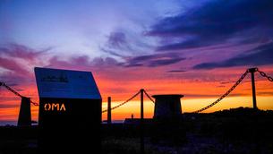 看板に切り抜かれたOMAの文字に夕焼け空の色が映る美しい大間港の夕景の写真素材 [FYI04118527]