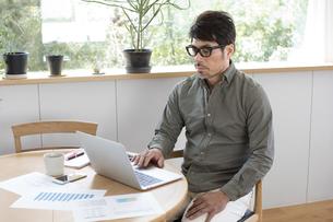 自宅でパソコンを使う男性の写真素材 [FYI04118528]