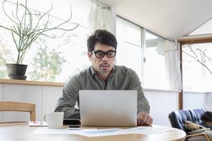 自宅でパソコンを使う男性の写真素材 [FYI04118532]