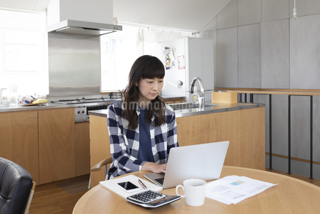 リビングでパソコンを使う女性の写真素材 [FYI04118548]