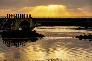佐渡島千畳敷の夕景。雲の切れ間から光が漏れる、幻想的な天使の梯子という現象が見えるの写真素材 [FYI04118604]