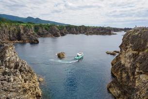 断崖が連なる景観が美しい景勝地、尖閣湾で海上を進む海中透視船グラスボードの写真素材 [FYI04118616]