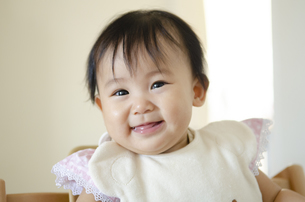 スタイをつけて笑っている赤ちゃんの写真素材 [FYI04118634]