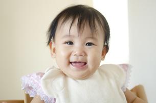 スタイをつけて笑っている赤ちゃんの写真素材 [FYI04118635]