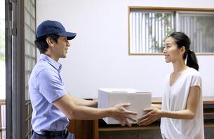 宅配物を渡す配達員と受け取る女性の写真素材 [FYI04118957]
