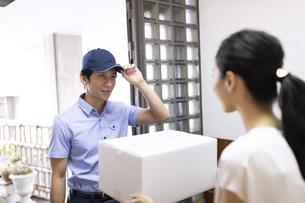 宅配物を届ける配達員の写真素材 [FYI04118960]
