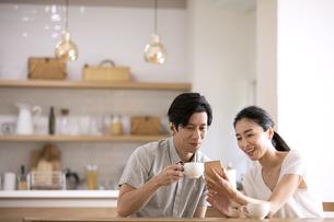 ダイニングでスマートフォンを見る夫婦の写真素材 [FYI04118966]