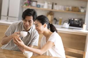 ダイニングでスマートフォンを見る夫婦の写真素材 [FYI04118967]