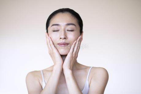 頬に手をあて目を閉じる女性の写真素材 [FYI04118968]