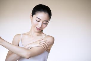 自分の腕をマッサージする女性の写真素材 [FYI04118970]