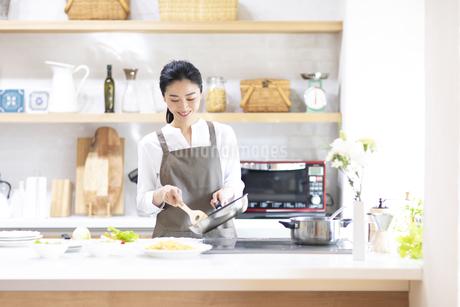 キッチンで料理を作る女性の写真素材 [FYI04118974]