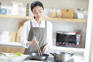 キッチンで料理を作る女性の写真素材 [FYI04118975]