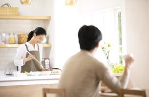 キッチンで料理を作る女性とテーブルで座る男性の後ろ姿の写真素材 [FYI04118976]