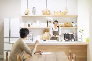 キッチンとダイニングとで会話する夫婦の写真素材 [FYI04118977]