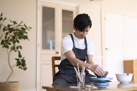 部屋で陶芸を楽しむ男性の写真素材 [FYI04118978]