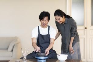 部屋で陶芸を楽しむ夫婦の写真素材 [FYI04118979]