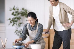 部屋で陶芸を楽しむ夫婦の写真素材 [FYI04118982]