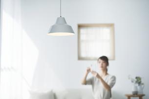 スマートフォンで家電を操作する女性の写真素材 [FYI04119170]