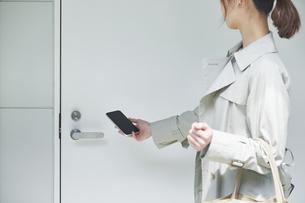 ドアにスマートフォンをかざす女性の写真素材 [FYI04119199]