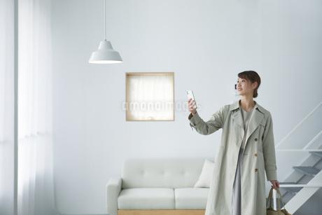 スマートフォンで操作する女性の写真素材 [FYI04119237]