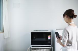 電子レンジを使う女性の写真素材 [FYI04119239]