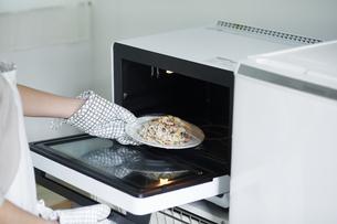 電子レンジを使う女性の写真素材 [FYI04119243]