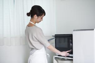 電子レンジを使う女性の写真素材 [FYI04119244]