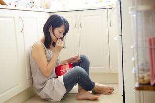 キッチンに座り込んでクッキーを食べている女性の写真素材 [FYI04119770]