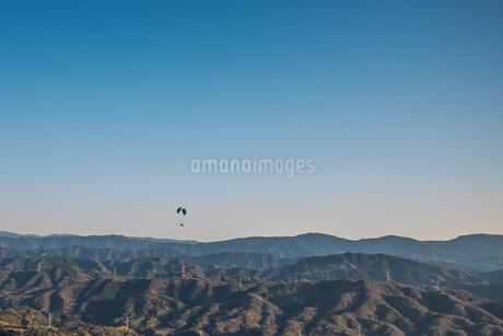 山脈の上を飛ぶパラグライダーを空撮の写真素材 [FYI04121515]