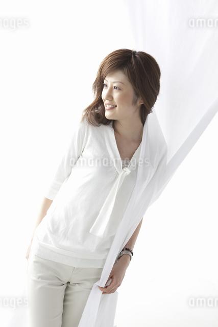 カーテン越しに微笑む女性の写真素材 [FYI04128948]