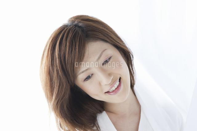 カーテン越しに微笑む女性の写真素材 [FYI04128949]