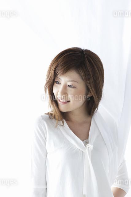 カーテン越しに微笑む女性の写真素材 [FYI04128951]