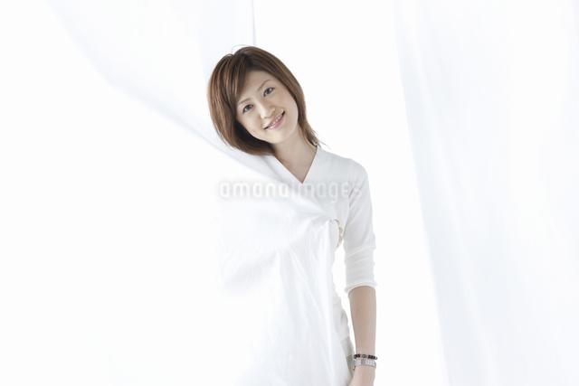 カーテン越しに微笑む女性の写真素材 [FYI04128952]