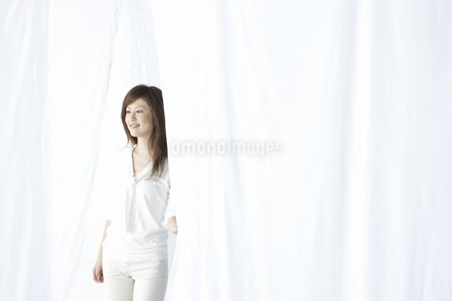 カーテン越しに微笑む女性の写真素材 [FYI04128954]