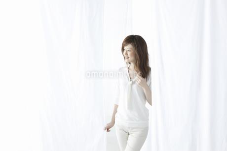 カーテン越しに微笑む女性の写真素材 [FYI04128956]